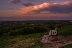 Coucher du soleil au-dessus de champ idyllique avec le banc abandonn? et le ciel nuageux rose dramatique photos libres de droits
