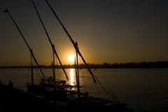 Coucher du soleil au-dessus de fleuve avec des fellucas Image stock