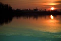 Coucher du soleil au-dessus de l'eau Image libre de droits