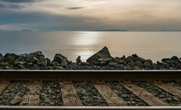 Coucher du soleil au-dessus de l'océan avec des voies et des roches de train dans le premier plan Image stock