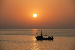 Coucher du soleil au-dessus de l'océan avec un bateau Photos libres de droits
