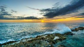 Coucher du soleil au-dessus de l'océan pacifique avec des vagues se brisant sur Rocky Shoreline sous le ciel coloré images libres de droits