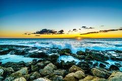 Coucher du soleil au-dessus de l'océan pacifique avec des vagues se brisant sur Rocky Shoreline sous le ciel coloré photo stock