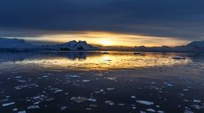 Coucher du soleil au-dessus de la lagune avec les icebergs et les montagnes de dérive de neige Image stock
