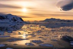Coucher du soleil au-dessus de la lagune avec les icebergs et les montagnes de dérive de neige Photos libres de droits