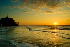 Coucher du soleil au-dessus de la mer avec le ciel nuageux image libre de droits