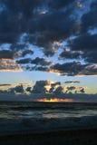 Coucher du soleil au-dessus de la mer derrière les nuages Photographie stock libre de droits