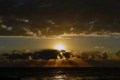 Coucher du soleil au-dessus de la mer derrière les nuages Photos stock