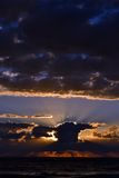 Coucher du soleil au-dessus de la mer derrière les nuages Photos libres de droits