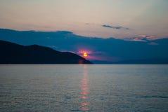 Coucher du soleil au-dessus de la mer et de la montagne Photo libre de droits