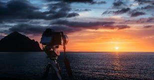 Coucher du soleil au-dessus de la mer, l'aérolithe occidental de côte du soleil au-dessus de l'horizon dans un ciel orange coloré Photographie stock libre de droits