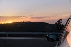 Coucher du soleil au-dessus de la montagne vue de l'extérieur d'une voiture Photos libres de droits