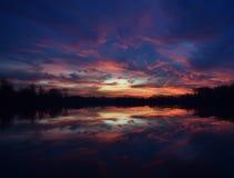 Coucher du soleil au-dessus de la réflexion de lac Photographie stock libre de droits