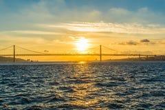 Coucher du soleil au-dessus de la rivière et du pont le vingt-cinquième avril Photo stock