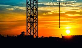 Coucher du soleil au-dessus de la ville avec une silhouette de grue Photos libres de droits