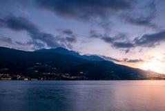 Coucher du soleil au-dessus de la ville de montagne située au lac Photographie stock