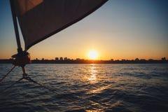 Coucher du soleil au-dessus de la ville du voilier Le treuil de voilier, la voile et la corde nautique font de la navigation de p Photographie stock libre de droits