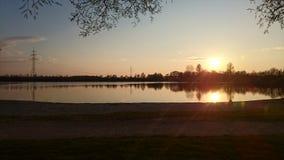 Coucher du soleil au-dessus de lac à Munich Photos stock