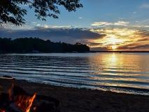 Coucher du soleil au-dessus de lac avec le feu de camp en été Photographie stock