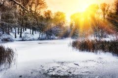 Coucher du soleil au-dessus de lac de forêt d'hiver Photographie stock libre de droits