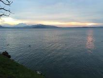 Coucher du soleil au-dessus de lac et de montagnes photos stock