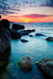 Coucher du soleil au-dessus de littoral rocheux Photo libre de droits