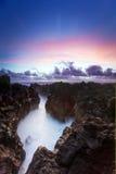 Coucher du soleil au-dessus de littoral rocheux Photographie stock libre de droits