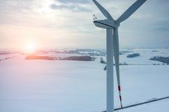 Coucher du soleil au-dessus de moulin à vent sur le champ en hiver Photographie stock libre de droits