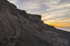 Coucher du soleil au-dessus de plage noire célèbre dans Santorini Image libre de droits