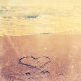 Coucher du soleil au-dessus de plage sur le rivage avec le coeur d'amour dans le sable Image stock