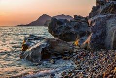 Coucher du soleil au-dessus de roche, de mer et de caillou images stock