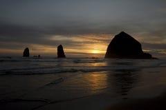Coucher du soleil au-dessus de roche de meule de foin en plage de canon Images libres de droits