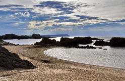 Coucher du soleil au-dessus de Rocky Antrim Coast silhouettant les îles rocheuses près du port de Balintoy Photo libre de droits