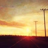 Coucher du soleil au-dessus de route avec la scène de pays de poteaux de télégraphe Photos libres de droits