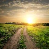 Coucher du soleil au-dessus de route de campagne Photos stock