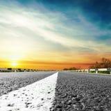 Coucher du soleil au-dessus de route goudronnée Photo stock