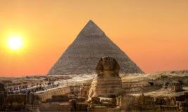 Coucher du soleil au-dessus de sphinx et de pyramide Image stock