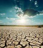 Coucher du soleil au-dessus de terre de sécheresse Image libre de droits