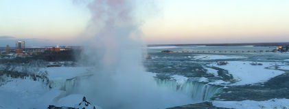 Coucher du soleil au-dessus des chutes du Niagara congelées Photographie stock libre de droits
