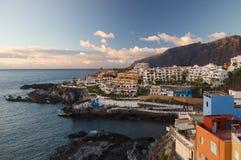 Coucher du soleil au-dessus des falaises de visibilité directe Gigantes et des stations de vacances de Puerto Santiago Photographie stock