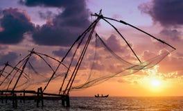 Coucher du soleil au-dessus des filets de pêche chinois à Cochin Photos stock