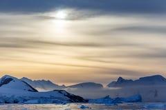 Coucher du soleil au-dessus des montagnes avec des glaciers et des icebergs de dérive à Photographie stock