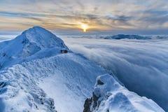 Coucher du soleil au-dessus des montagnes et des nuages en hiver Photographie stock