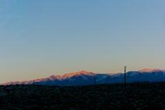 Coucher du soleil au-dessus des montagnes neigeuses Images libres de droits