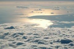Coucher du soleil au-dessus des nuages de fenêtre d'avion Photos stock