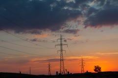 Coucher du soleil au-dessus des poteaux de puissance, des immeubles et d'un arbre Photo libre de droits