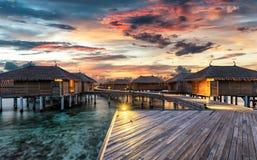 Coucher du soleil au-dessus des villas maldiviennes de l'eau image stock