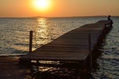 Coucher du soleil au-dessus du Golfe et des personnes sur le pilier Photographie stock