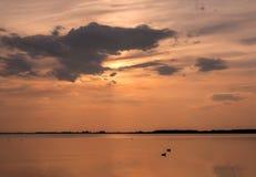 Coucher du soleil au-dessus du lac avec des silhouettes de deux canards Images stock
