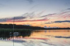 Coucher du soleil au-dessus du lac avec le ciel et le bateau étonnants Photo libre de droits